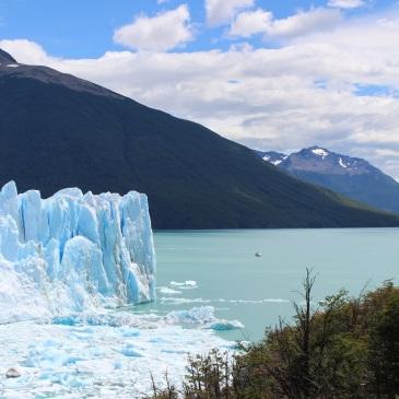 Le bateau de touristes parait minuscule à côté du glacie