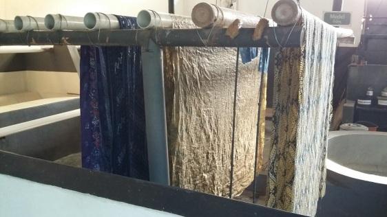 Etape 3 : une fois la cire sèche, on trempe le tissu dans des bains de teintures puis on le passe à l'eau chaude pour enlever la cire